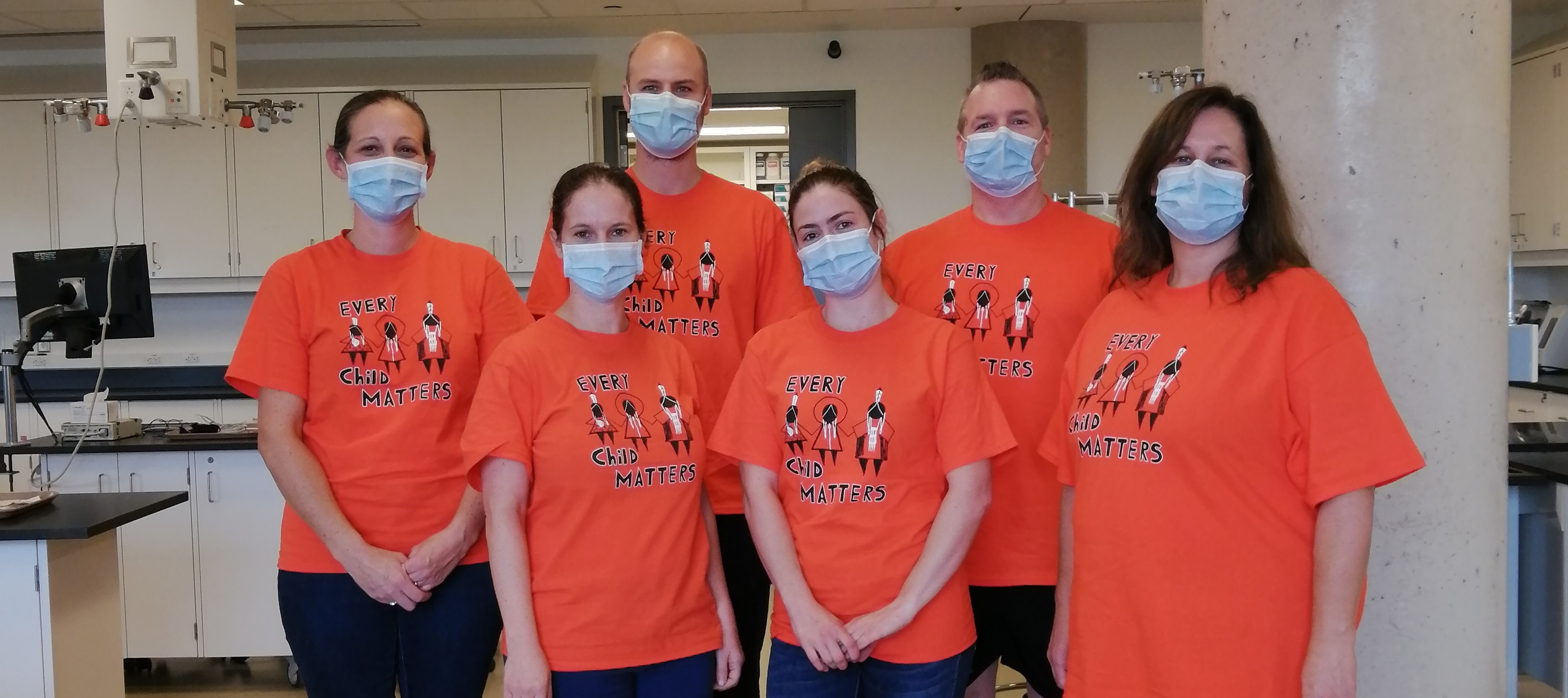 Six staff members are wearing orange t-shirts that read Every Child Matters